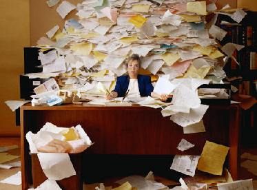 overwhelmed employee messy desk procrastination workplace office